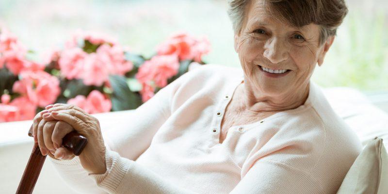 Doamnă în vârstă cu baston fericită