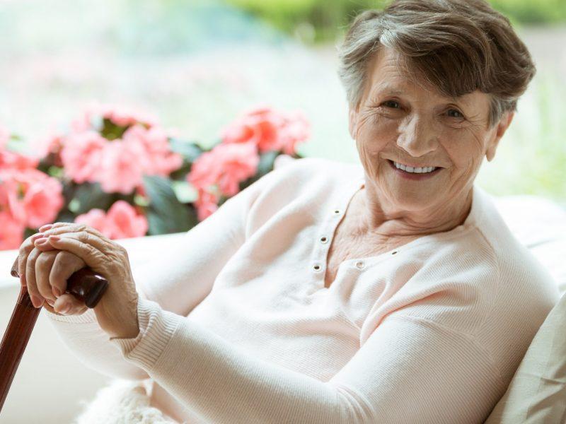 Gelukkige oudere dame met wandelstok